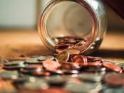 Loose change spilling out of a jar.