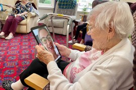 Nora, 101, speaking with her granddaughter following a donation of technology by Stockport Council