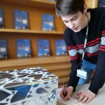 Student Michael Jarkowski signs a pledge card for Love Our Colleges Week