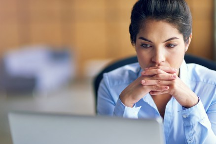 Shot of a young businesswoman looking stressed while working on her