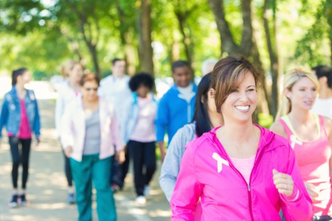 Mature Caucasain brunette woman is smiling while walking in charity marathon race event. She is wearing pink athletic clothing and a breast cancer awareness ribbon. Diverse teams of people are walking behind her to raise money for breast cancer research