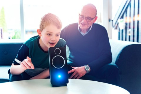 A boy sits in a sofa with his grandfather and they are bonding with help of consumer electronics. In front of them on a table stand a digital assistant, which is an intelligent loudspeaker with built-in microphone. The digital assistant can help answer questions and enable the family to control internet of things such as lightbulbs and door locks with voice commands