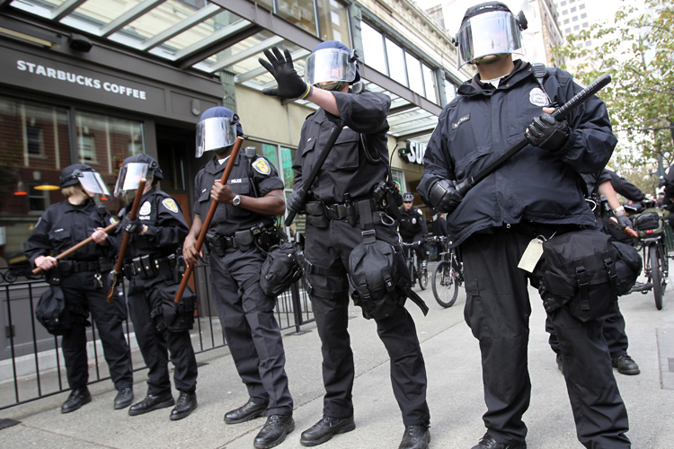 Seattle police officers, wearing riot gear, guard a Starbucks coffee shop during May Day demonstrations that went violent in downtown Seattle May 1, 2012. Several hundred demonstrators, including hundreds in black masks, hoods and armed with bats destroyed the windows of a Wells Fargo Bank, NikeTown and an American Apparel store during one of the numerous marches throughout downtown Seattle. REUTERS/Anthony Bolante (UNITED STATES - Tags: CIVIL UNREST POLITICS CRIME LAW) - RTR31HN4