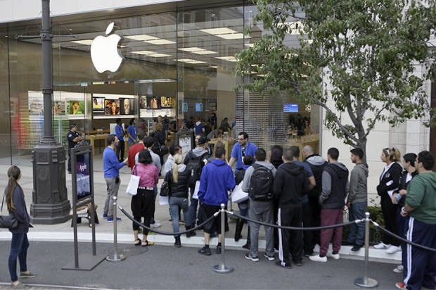 Customers wait in line to buy the latest versions of the iPhone during the opening day of sales of the iPhone 5s and iPhone 5C at the Apple store at the Americana at Brand mall in Glendale, Calif., Friday, Sept. 20, 2013. (AP Photo/Damian Dovarganes)