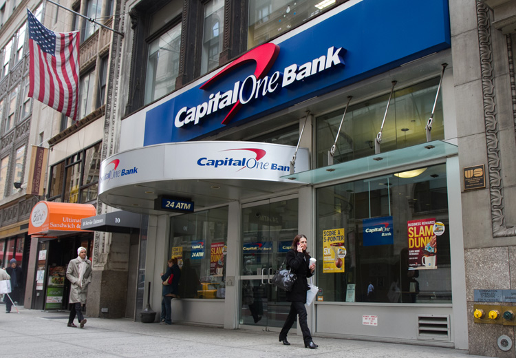 People walk by a Branch of the Capital One bank located on Fifth Avenue in Manhattan on March 15. (Benjamin Chasteen/The Epcoh Times)