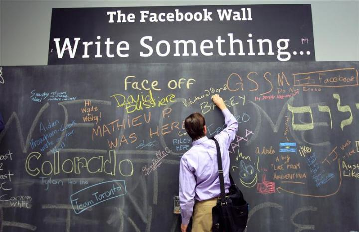 An employee writes a note on the message board at the new headquarters of Facebook in Menlo Park, California January 11, 2012. The 57-acre campus, which formerly housed Sun Microsystems, features open work spaces for nearly 2,000 employees on the one million square foot campus, with room for expansion. Picture taken January 11, 2012. REUTERS/Robert Galbraith  (UNITED STATES - Tags: SCIENCE TECHNOLOGY MEDIA TPX IMAGES OF THE DAY)