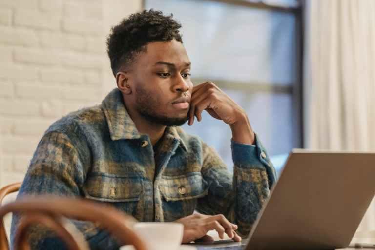 serious black man working on laptop in workspace
