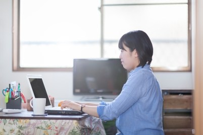 A young Japanese woman is doing her work on her laptop at her home-office.