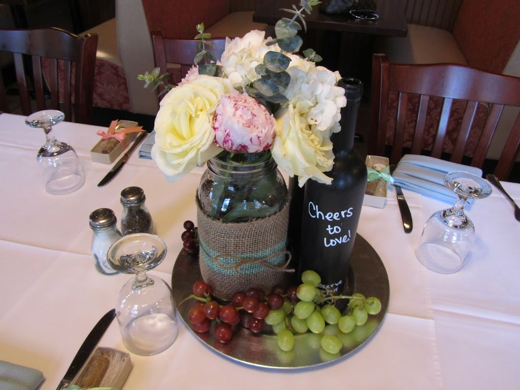 Handmade floral centerpieces for wine-inspired wedding using large mason jars, burlap and peonies