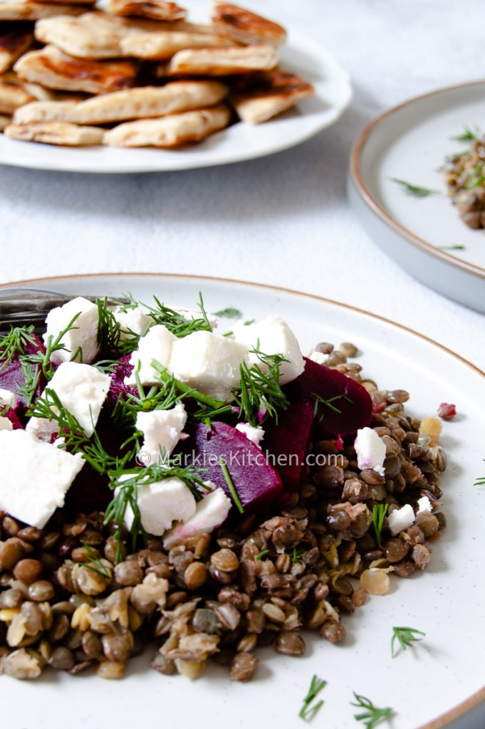 a close-up picture of lentil beetroot and feta salad served with Greek style pita bread