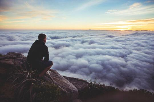 Man sitting on cliff looking out over clouds