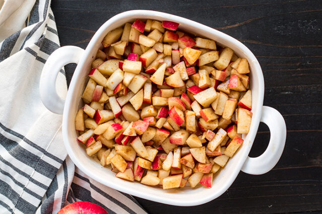 cinnamon and coconut sugar coated apples layered into a baking dish for apple dump cake