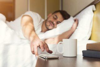 sleeping man hitting snooze on his phone