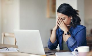 woman at her laptop showing signs of burnout