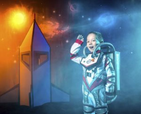 The little boy dressed in space costume and a astronaut's jetpack on back is standing near a rocket. The boy is playing astronaut. He looking at the camera and waving his hand. Chalk drawing of a outer space on background. Studio shooting in light haze