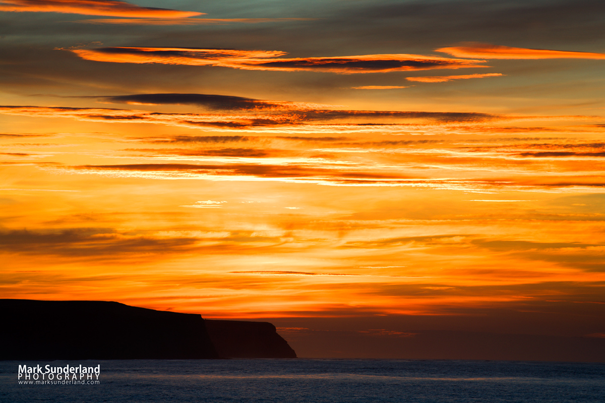 Sunset across the bay to Sandsend from the pier at Whitby, North Yorkshire