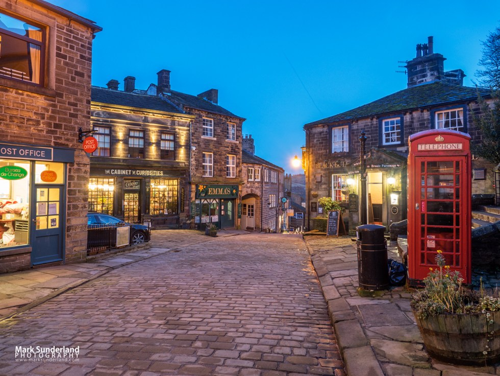 Lights coming on along the cobbled Main Street in Haworth Village at dusk, West Yorkshire