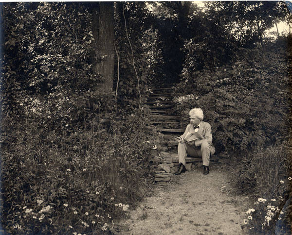 Samuel Clemens seated on the steps leading up to his study at Quarry Farm, East Hill, Elmira, New York.