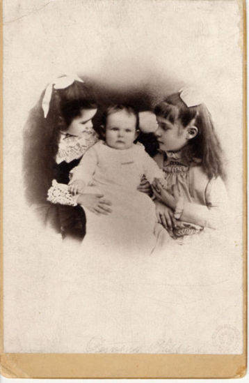 Samuel and Olivia Clemens' three daughters. Clara and Susy looking at baby Jean. Left to right, Clara, Jean and Susy.