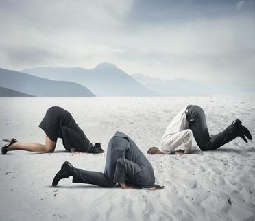 drei Leute in Businesskleidung stecken den Kopf in den Sand