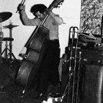Roberto Miranda demonstrating slap bass (he had developed a piece back then that he'd play as a solo during concerts demonstrating slap bass technique -- in this shot he has the bow, and I don't remember the bow being a part of the slap bass number . . . ) -- November 28, 1976 -- Little Big Horn -- photo by Mark Weber