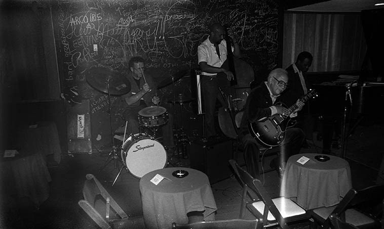 """John Collins Quartet at Donte's, North Hollywood -- Ed Shaughnessy sitting in ---- the Quartet this  night was: Dick Berk, drums; John B. Williams, bass; Gildo Mahones, piano -- May 24, 1982 --  photo by Mark Weber ---- John Collins (1913-2001) was a swing-to-bop era guitarist  who made his  first records in 1931, was with Roy Eldridge 1936-1940, made records with Mildred Bailey and  Billie Holiday, Don Byas, Hot Lips Page, Pete Johnson, made the Decca Tatum sides,  JATP 1946, recorded one of the earliest versions (1946) of """"Epistrophy"""" w/ Kenny Clarke's 52nd Street Boys  that included Bud Powell & Fats Navarro, too many people to list, Illinois Jacquet, Tadd Dameron, Coleman  Hawkins, Artie Shaw, Wild Bill Davis, Duke Ellington, and a long tenure (1951-1965) with Nat King Cole,  among OTHERS, but most notably was his close association with the Master of Time & Space (Lester  Young) in small groups on 52nd Street during 1940 & 1941 and as part of Lester's short-lived orchestra  during that time -- So, when John Collins played Donte's we were all there"""