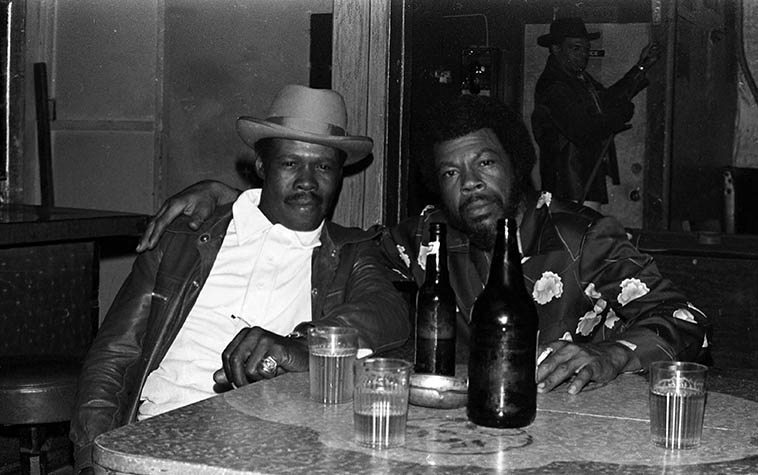 Smokey Wilson (w/ hat) and another guitar slinger Curtis Griffin at Smokey's Pioneer Club at 88th & Vermont, Los Angeles -- June 1978 -- photo by Mark Weber -- I love that pool cue being chalked behind them ---- For whatever reasons I never did do a lot of college (stay in school, my children, it's important), but I like to tell people it's because I was hanging out in clubs like this, instead ---- the music was hard & tough, and the beer was good, and the culture of Watts and environs was fascinating ----- One afternoon hanging out at the Pioneer I got to see where Smokey hid all his money: He lifted up the green slate of the pool table (I didn't know those were removable) and there was his cash money ----- Who could deny the poetry of the blues . . . .