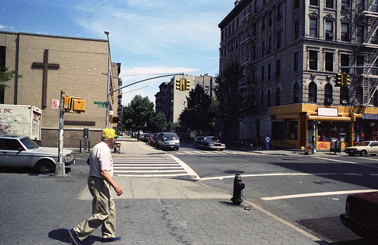 I don't know if you can see it clearly but that street sign says Charlie Parker Place / Avenue B and that guy in the yellow cap is about to cross 7th Street heading north -- July 1, 1997 ---- photo by Mark Weber ---- In 1992 Avenue B between 7th and 10th Streets was rechristened Charlie Parker Place as Bird & Chan lived at 151 Avenue B the years 1950-1954 facing Tompkins Square Park
