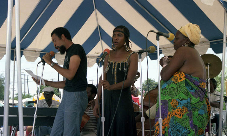 Pan Afrikan Peoples Arkestra: Horace Tapscott (piano), poet Kamau Daaood, BJ Crowley & Linda Hill (vocals), Louis Spears (cello), Donald Dean (drumset) – July 15, 1984 Watts Towers Jazz Festival ----- others in Arkestra that day: Roberto Miranda, Al Hines, & David Bryant (basses), Larry Gales (cello), Dadesi Arthur Wells (sax) – photo by Mark Weber