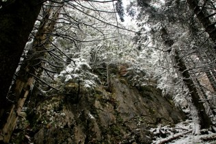 A rock face covered in a thin layer of snow