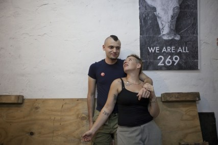 Israeli activists Sasha Boojor and Tal Gilboa are seen during a gathering of activists for Animal rights in a club in Tel Aviv, Wednesday, June 26, 2013. Boojor squirmed and struggled as black-clad masked men yanked him out of a cage and branded him with a hot iron. While the smell of seared flesh was disturbing, he said, this shocking and painful act was worth it: He was showing solidarity with animals that suffer branding on farms around the world. (AP Photo/Dan Balilty)
