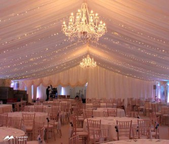 Image of Marquee with luxury chandeliers, and a half curtain (half-up) at rear of room