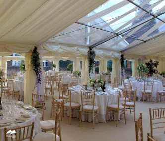 Image of a luxury marquee prepared for a wedding with beautiful table settings, tiny lights in the roof and a transparent section of roof to bring light into the marquee