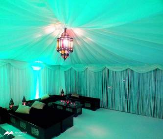 Image of interior Arabian theme marquee with center lantern chandelier and fringe curtains