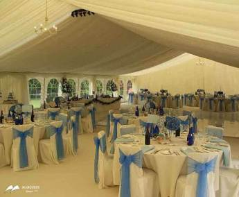 Image of 5ft round tables, white chairs with blue ribbons, starlight LED lighting, ivory swags