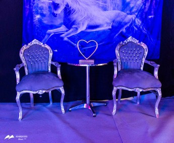 Image of silver velvet chairs under blue lighting