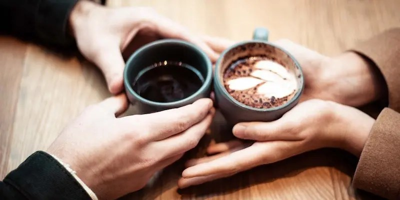 couple holding hands and coffee