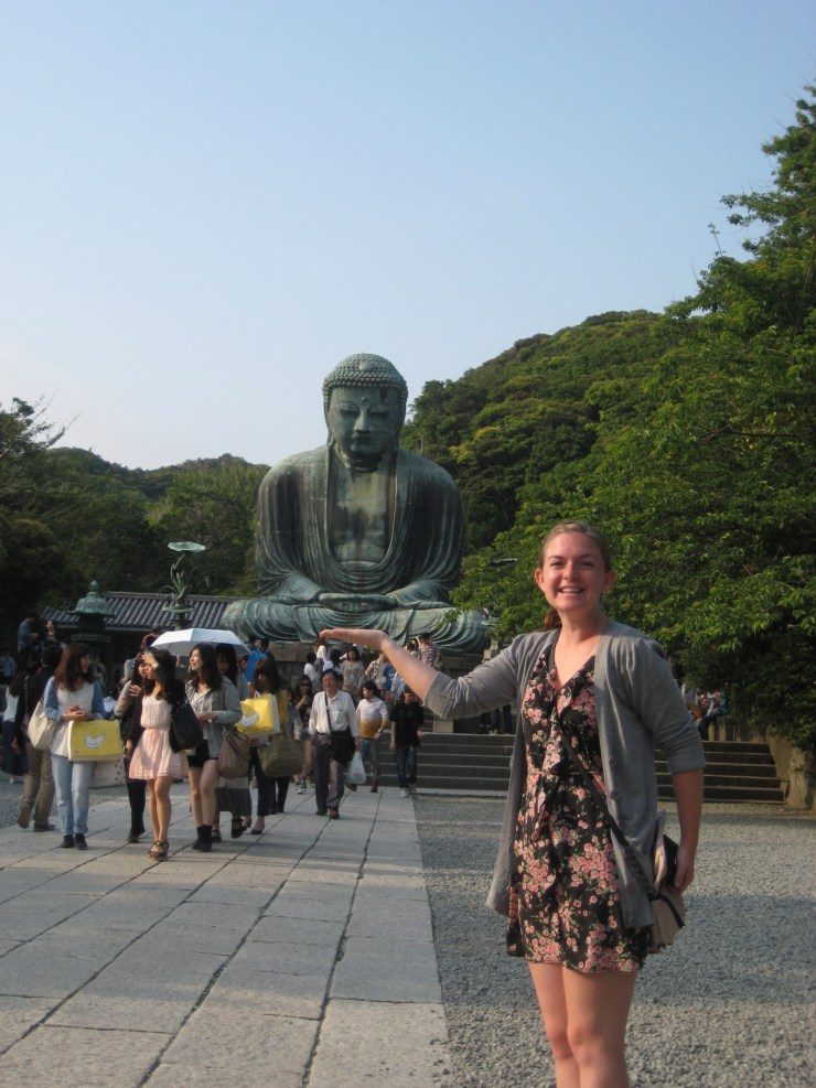 Kara posing with the Great Buddha of Kamakura, in Japan.