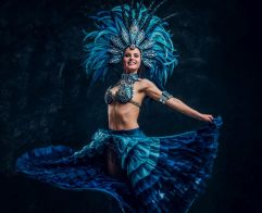 Talented joyful dancer in red feather costume is posing at small dark studio.