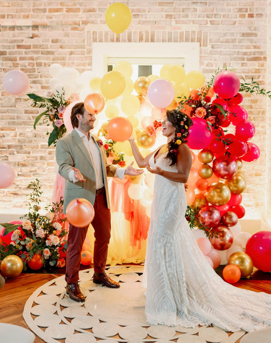 Whimsical and Colorful Bride and Groom with Orange, Pink, Yellow and Gold Balloon and Fringe Ceremony Backdrop   Tampa Bay Wedding Photographer Dewitt for Love   St. Pete Modern Industrial Wedding Venue Red Mesa Events