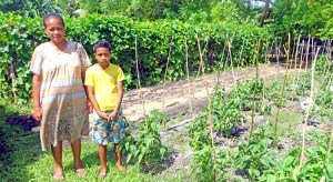 Marilla Capelle with her son Nilo Lolin by their expansive farm in the Iolap area of Laura, Majuro. Photo: Kelly Lorennij.