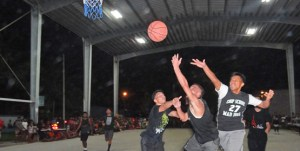 Marshalls Christian High School's Jonathan Mawilong weaved between two Majuro Cooperative High School defenders to score during a game at the SSG Solomon Sam Sports Center at the College of the Marshall Islands. Photo: Hilary Hosia.