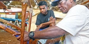 Waan Aelon in Majol's master canoe builder Binton Daniel and a trainee work on an outrigger canoe that will be hung in the lobby of the new Marshall Islands Marine Resources Authority headquarters building that is soon to open. Photo: Hilary Hosia.