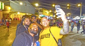 Do It Best Manager Larry Hernandez, Jr. (foreground) was in a festive mood at the Block Party, shooting selfies with friendly party-goers New Year's Eve in Uliga. Photo: Hilary Hosia.