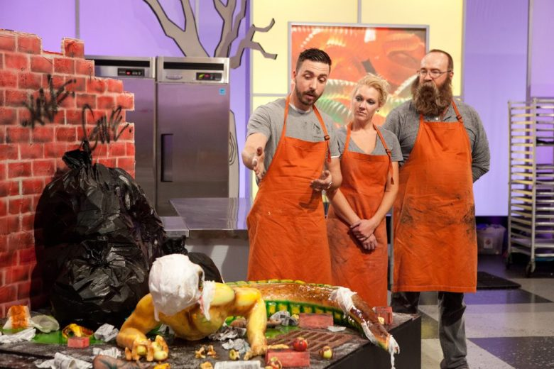 "Orange team's Adam Bierton, far left, gestures as he talks about his team's creation ""Half Man, Half Monster"", as seen on Food Network's Halloween Wars, Season 5."