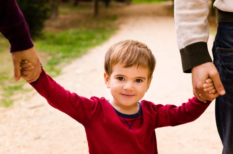 Primer plano de un niño mirando a cámara, sonriendo, agarrado a las manos de papá y mamá.