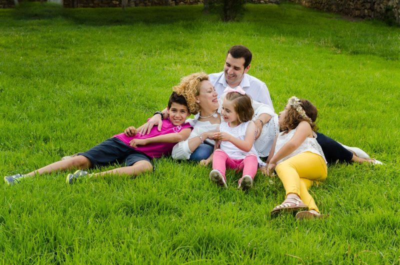 Una familia compuesta por cinco personas está sobre un césped en Cieza. Papá está sentado y, sobre él está tumbada mamá. Los tres niños están tumbados encima de ellos. Se miran entre ellos y ríen