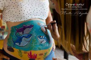 Fotografía de Susana de Colorehadas dando el último retoque al diseño de la familia tiburón dibujado sobre una barriga embarazada