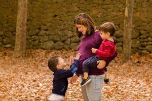 Mamá embarazada con un hijo en brazos en un lateral y en frente de ella el hijo mayor acariciándole la barriga. Están en un parque lleno de hojas marrones en otoño