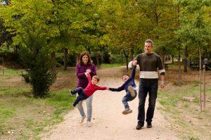 Familia de cuatro, cogidos de la mano. Mamá y papá están en los laterales y los niños en medio. Están jugando a lanzar los niños al aire sin soltarse de las manos. Están en un parque en otoño